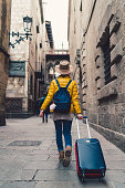 Rear view of young woman pulling a suitcase while walking in Barcelona