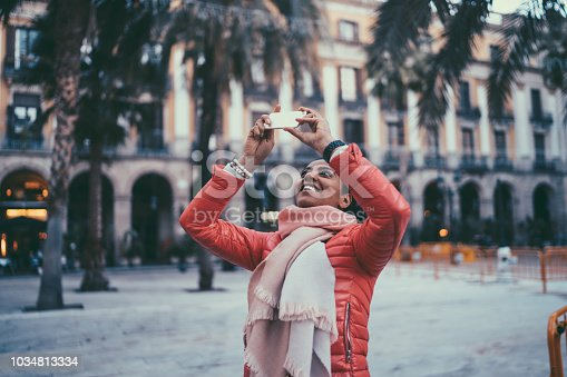 Mixed race woman taking photos in Barcelona with smartphone