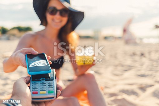 Young woman on summer vacation paying with smartphone on the credit card reader