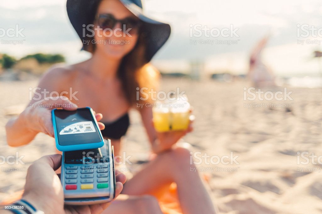 Tourist woman at the beach bar making mobile payment for drinks stock photo