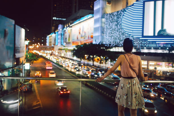 Tourist woman enjoys the view at Siam Square in Bangkok, Thailand Young traveler woman relaxing and enjoying the beautiful view at Siam square, Bangkok's Skytrain station. thailand mall stock pictures, royalty-free photos & images