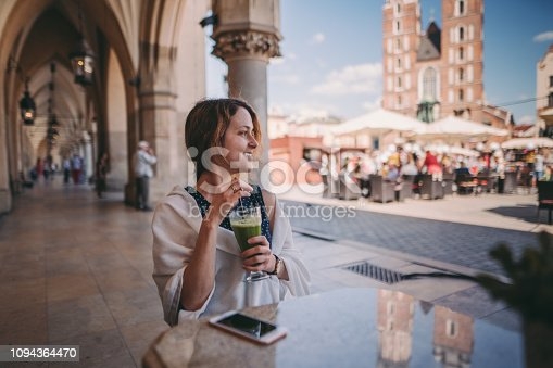 Relaxed woman at cafe drinking green smoothie and enjoying the old town of Krakow