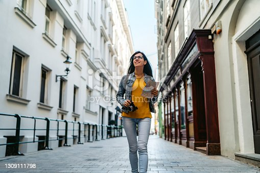Young Caucasian beautiful tourist woman exploring Vienna with map and camera.