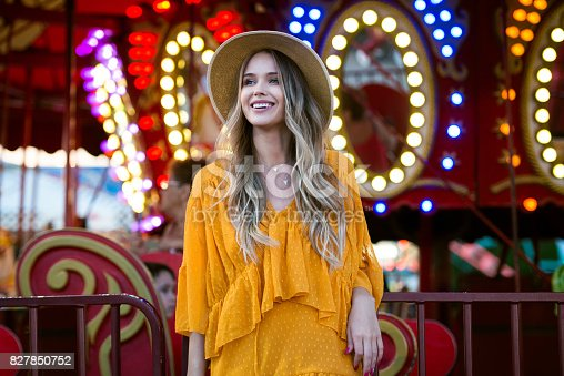 Beautiful smiling tourist woman having fun at an amusement park at hot summer day trip in New York, USA