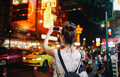 Young tourist woman enjoying walking on the streets of Bangkok in the evening, through the famous streets of Bangkok's Chinatown.