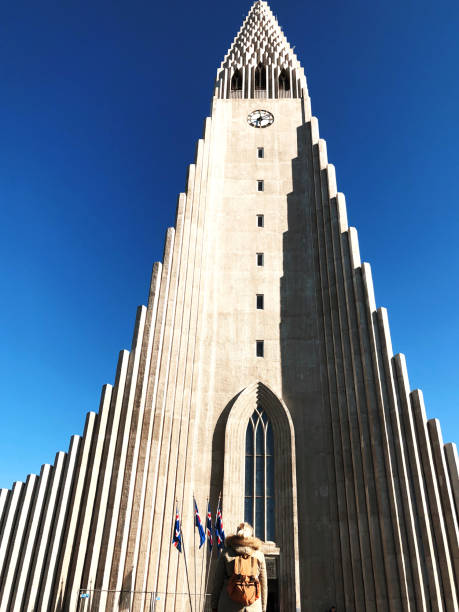 Tourist woman in front of Clock Tower church in Reykjavik Tourist woman in front of Hallgrimskirjka Clock Tower church in Reykjavik Hallgrímskirkja church stock pictures, royalty-free photos & images