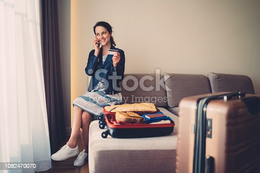 Smiling woman in hotel making reservations on the phone