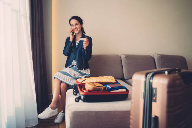 Tourist woman in hotel room making credit card reservation for flight Smiling woman in hotel making reservations on the phone making a reservation stock pictures, royalty-free photos & images