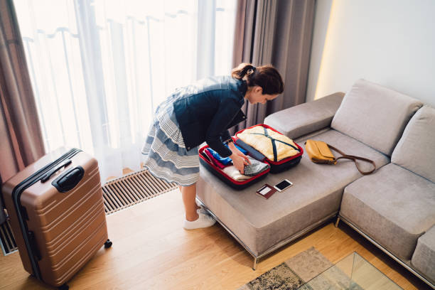 tourist woman in luxury hotel packing the suitcase before leaving - oggetti personali foto e immagini stock