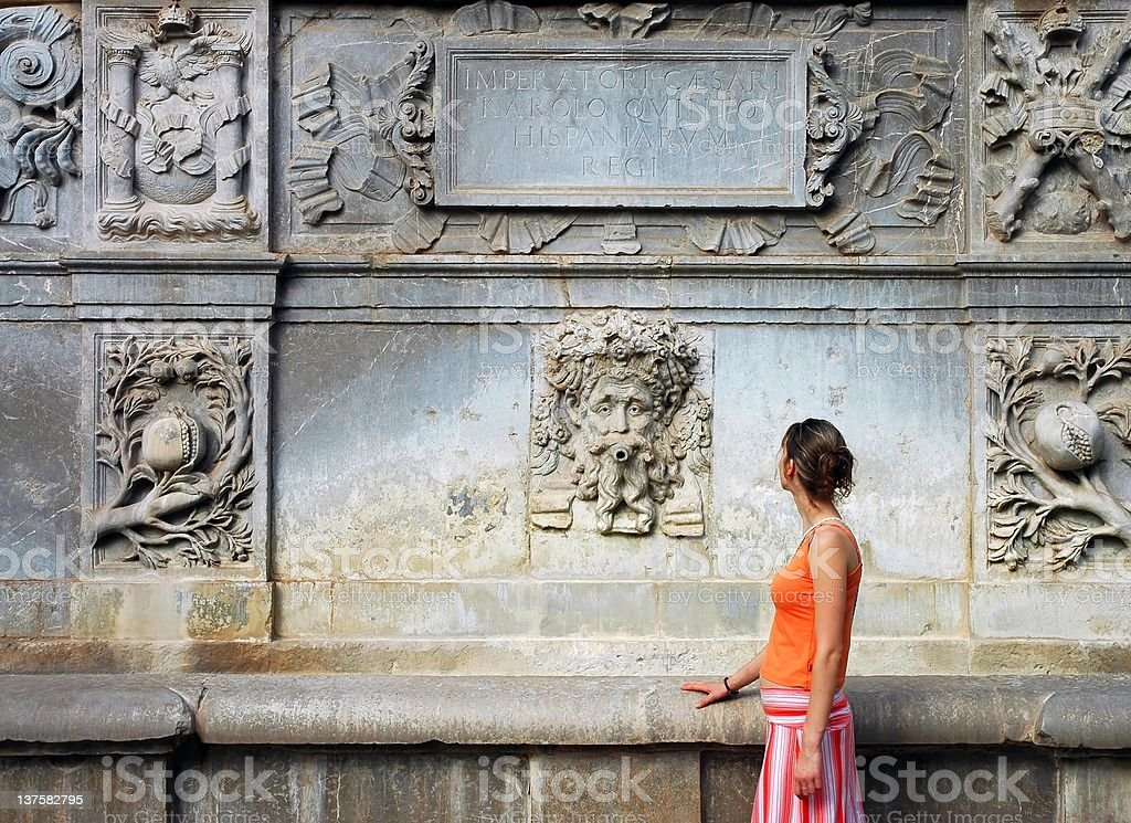 tourist woman in orange by the ancient artistic wall stock photo