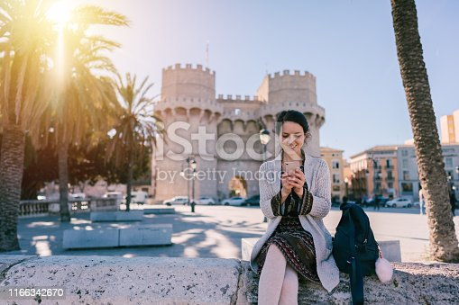 Happy woman enjoying vacation in Valencia and texting on phone