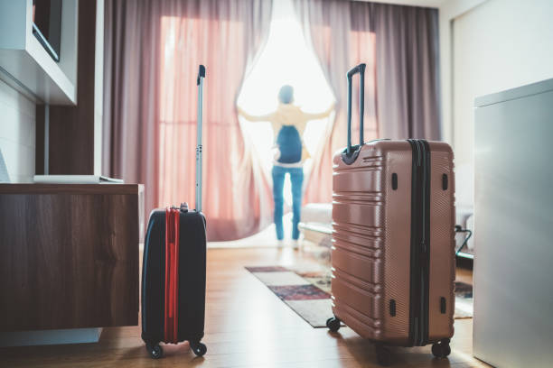 Tourist woman just arriving in the hotel room Rear view of tourist in hotel looking through the window carry on luggage stock pictures, royalty-free photos & images