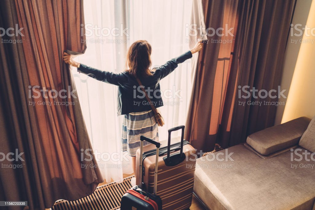 Rear view of tourist in hotel looking through the window