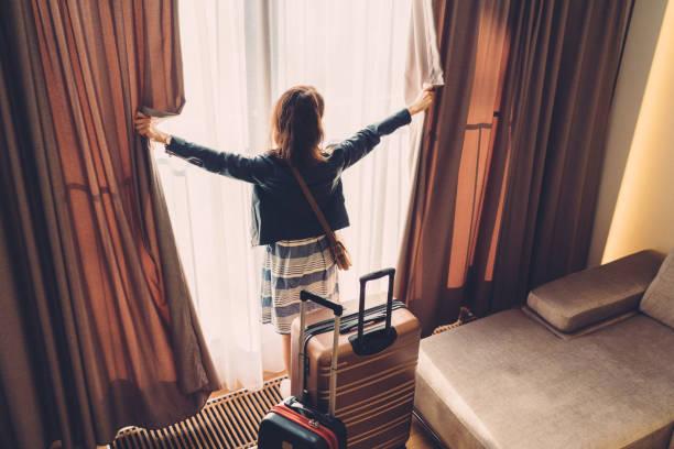 toeristen vrouw net aangekomen in de hotelkamer - raam bezoek stockfoto's en -beelden