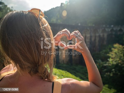 Traveler making heart with hands in front of the famous nine arch bridge in Sri Lanka sharing love