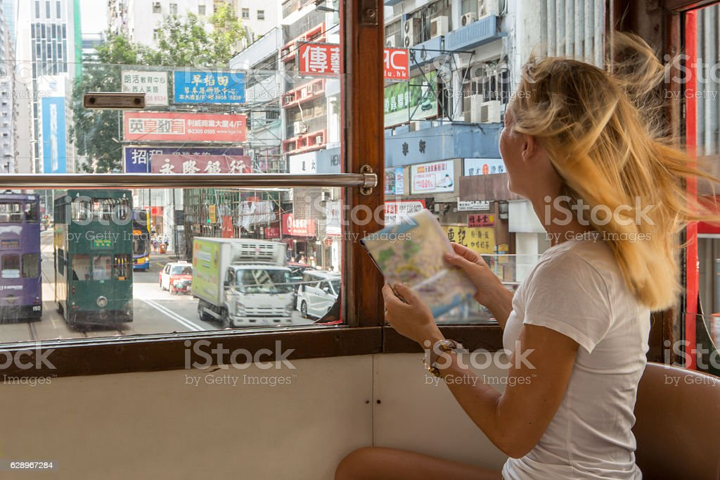 Tourist woman on cable car looks at Hong Kong map stock photo