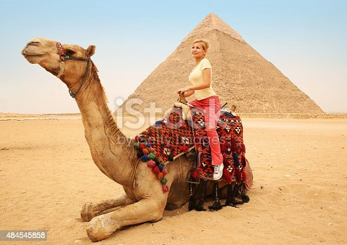883177796istockphoto Tourist woman on camel in Giza. Blonde near Pyramid, Egypt 484545858