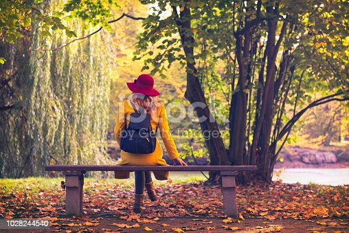 Girl wearing yellow coat and red hat relax in nature