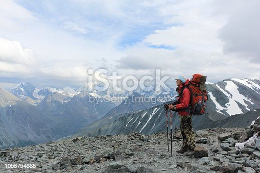 istock Tourist woman standing on top of the Pass Kara-Turek, against the Belukha Mountain, Altai, Russia 1058754668