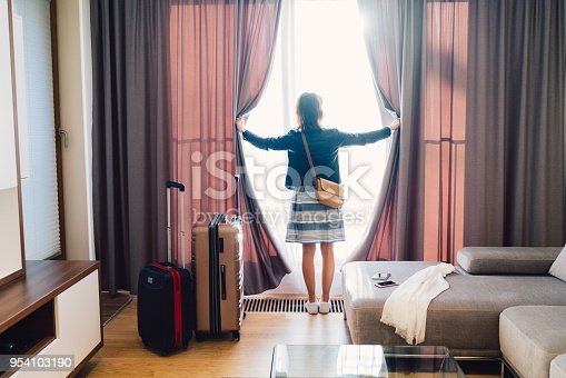 Rear view of tourist in the hotel room pulling the curtains to see the view