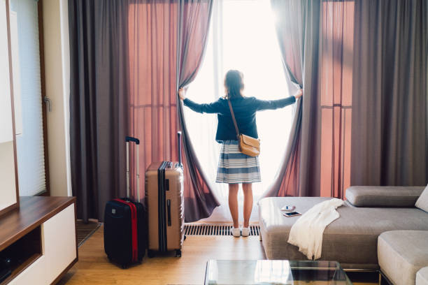 Tourist woman staying in luxury hotel Rear view of tourist in the hotel room pulling the curtains to see the view luxury hotel room stock pictures, royalty-free photos & images