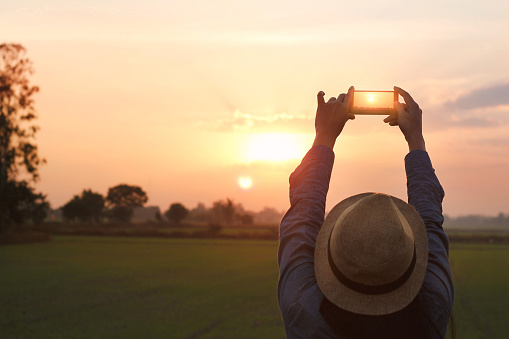 Tourist woman taking a photo with smartphone on sunset nature background