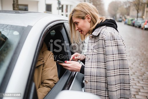 918377954 istock photo Tourist Woman talking to an uber driver 1206819388