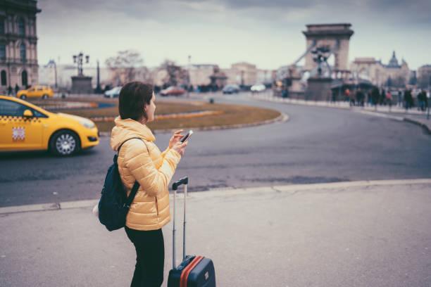 tourist-frau in europa unterwegs und handy zur navigation verwenden - trolley kaufen stock-fotos und bilder