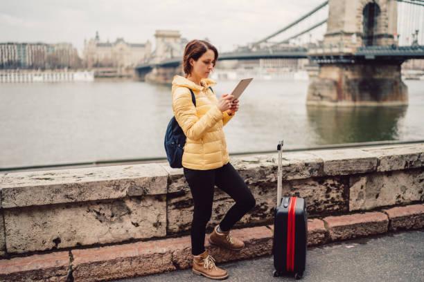 tourist-frau in europa unterwegs und tablet zur navigation verwenden - trolley kaufen stock-fotos und bilder