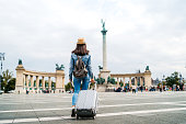 Young caucasian slim tourist woman visiting Budapest. Walking over Heroes' Square with luggage and map.