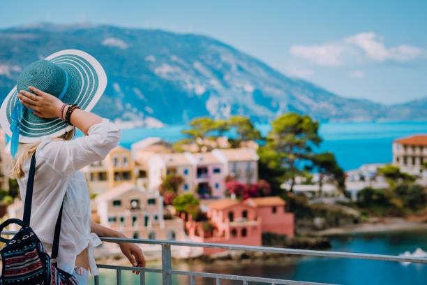 turist kvinna som bär blå solhatt och vita kläder njuter utsikt över färgglada lugna byn assos solig dag. snygg kvinna besöker kefalonia sommartid i grekland resor semester - grekiska övärlden bildbanksfoton och bilder