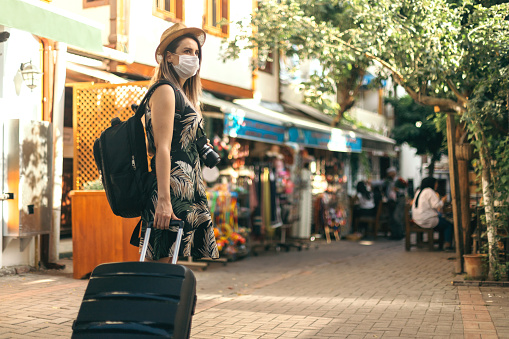 Tourist woman wearing protective face mask and  exploring new place