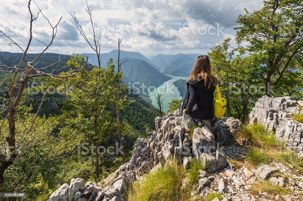 A tourist woman with a backpack sits on top of the mountain on Banjska Stena viewpoint royalty-free stock photo
