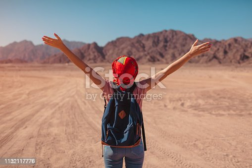 istock Tourist woman with backpack wearing scarf on head. Happy traveler admiring Sinai Desert and mountains 1132117776