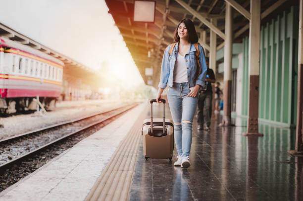tourist woman with luggage at the train station stock photo