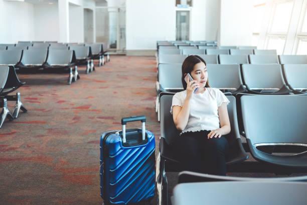 tourist women using phone at international airport waiting for boarding - donna valigia solitudine foto e immagini stock