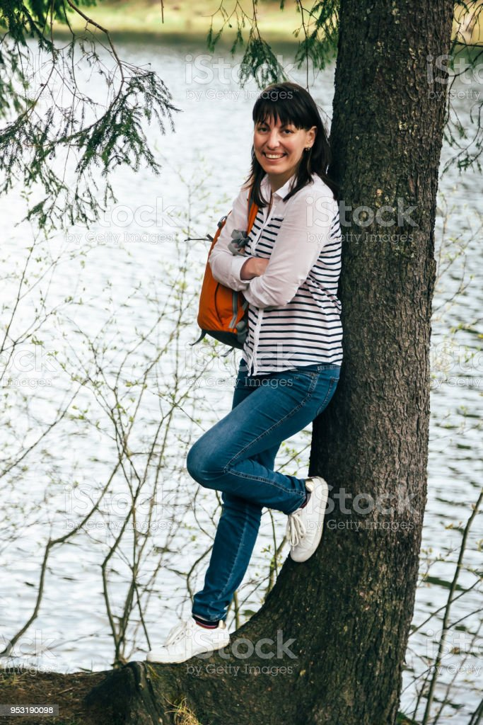 Tourist young smiling girl with orange backpack standing near to the big tree on the bank of the mountain lake stock photo