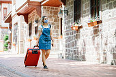 tourist Young woman wearing medical mask and walking with suitcase on the street