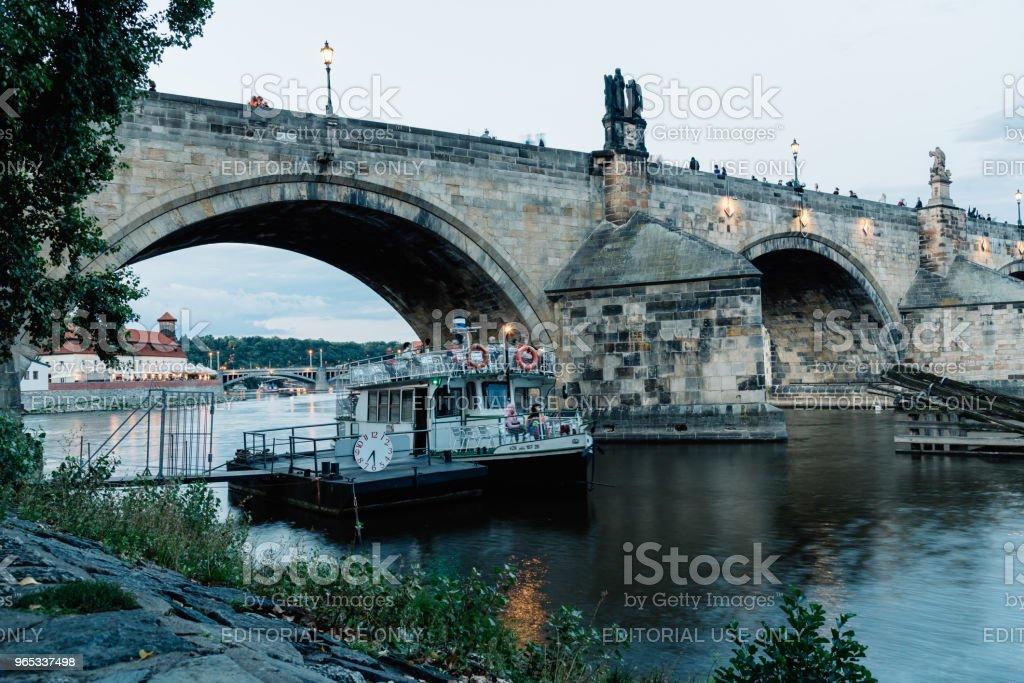Touristic boat in Vltava River under Charles Bridge in Prague royalty-free stock photo