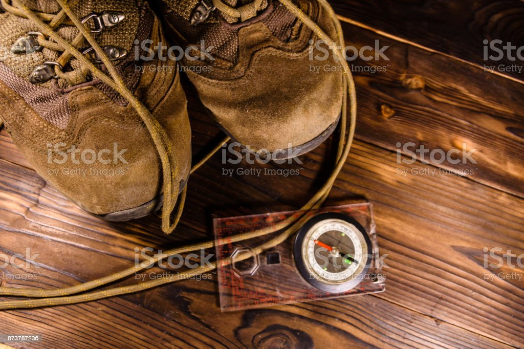Touristic magnetic compass and boots on wooden table stock photo