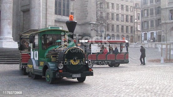 GENEVA, SWITZERLAND - NOVEMBER 20, 2010: Red Tourist Train in Old Retro Style is Driving Tourist Passengers to Explore the City and to See the Sightseeing's of Geneva in Swiss.