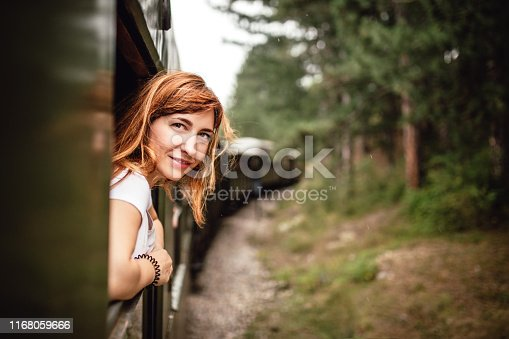 Happy smiling redhead woman looks out from window traveling by train