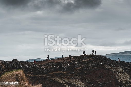 Silhouettes of tourists against the sky on the edge of the Kerid crater