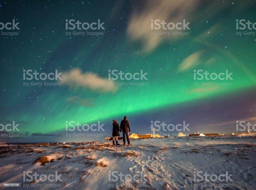 Tourists admire the Aurora Borealis.  Reine, Norway.  Lofoten Islands stock photo