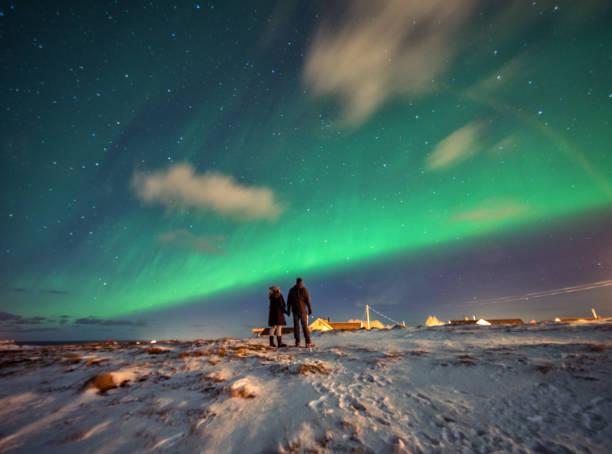 Turistas admiram a Aurora Boreal.  Reine, Noruega.  Ilhas Lofoten - foto de acervo