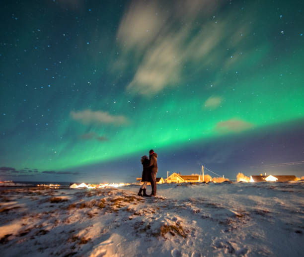 Tourists admire the Aurora Borealis.  Reine, Norway.  Lofoten Islands stock photo