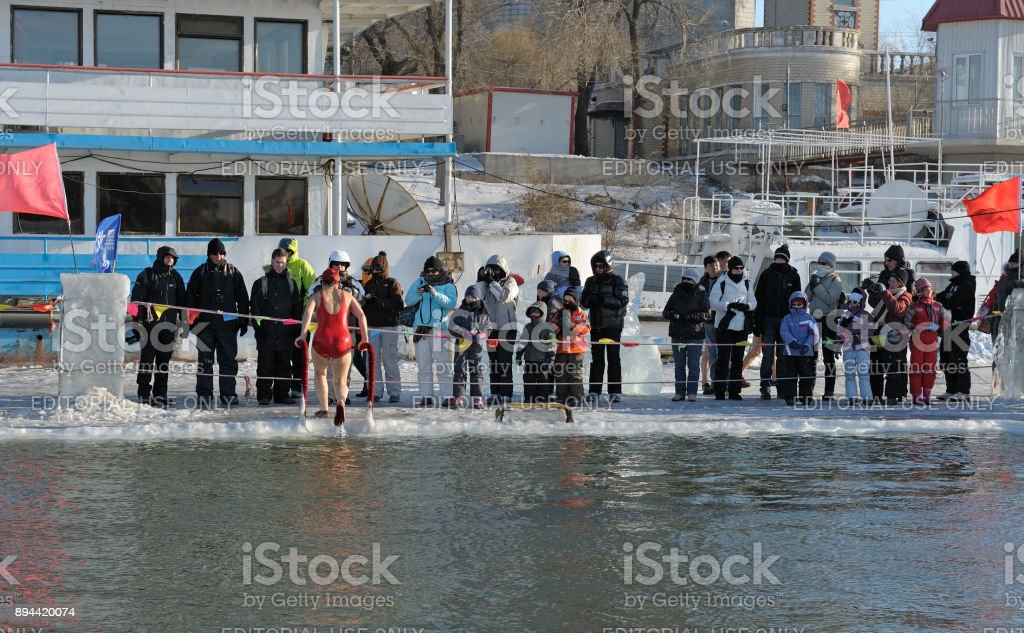 Tourists admiring Harbin's local people taking a dip in hole cut in icy Songhua river during famous, annual Harbin Ice & Snow World Festival. Air temptature is minus 22 degree Farenheit (-30°C)! stock photo