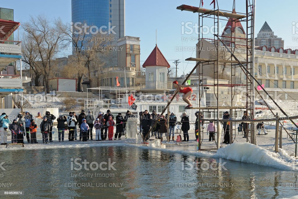 Tourists admiring Harbin's local people taking a dip in hole cut in icy Songhua river during famous, annual Harbin Ice & Snow World Festival. Air temperature is minus 22 degree Farenheit (-30°C) ! stock photo