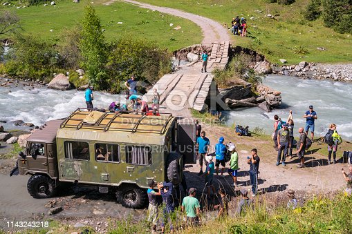 Karakol, Kyrgyzstan - Avgust 15, 2017: Tourists arrived in adapted military truck as an off-road vehicle for trekking in mountain Karakol, Kyrgyzstan. This is the starting trekking point  to Ala-Kul Lake as popular a three-day trekking trip from Karakol in wild, cold and beautiful nature and back through Altyn Arashan valley.