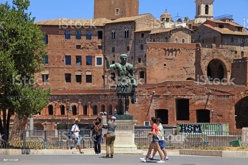 Tourists and bronze statue of Emperor Trajan, Rome, Italy. stock photo